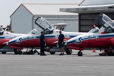 Snowbird's technicians prepare the planes for the show. Notice that some of them are on the ground, under the plane, using Windex to clean and polish the planes so that they shine during the show.