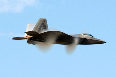 At transonic speeds a special form of vapor ring forms around an aircraft called the Prandtl-Glauert singularity. This is one of a series of 4 photos that demonstrate the Prandtl-Glauert singularity on a F-22 Raptor as it makes a high speed pass.