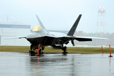 F-22 Raptor s/n 101 sits on the tarmac at Dobbins ARB on Friday. The rain on Friday cancelled out the practice flights for media day. The Lockheed Martin factory where the F-22 Raptors are built can be seen in the background.