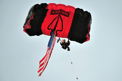 """The U.S. Army Airborne Special Operations' """"Black Daggers"""" open the air show with the American Flag"""