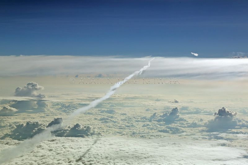 Long aircraft contrail. Smaller one to the right. As seen from above both.