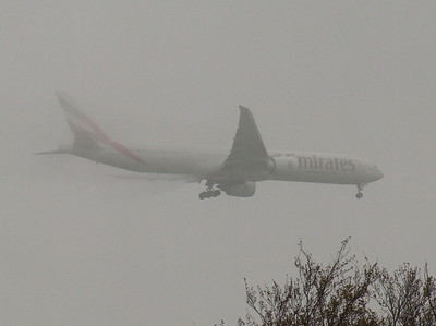 An Emirates  Boeing 777-31H/ER bursting out of the mist on approach to Glasgow Airport