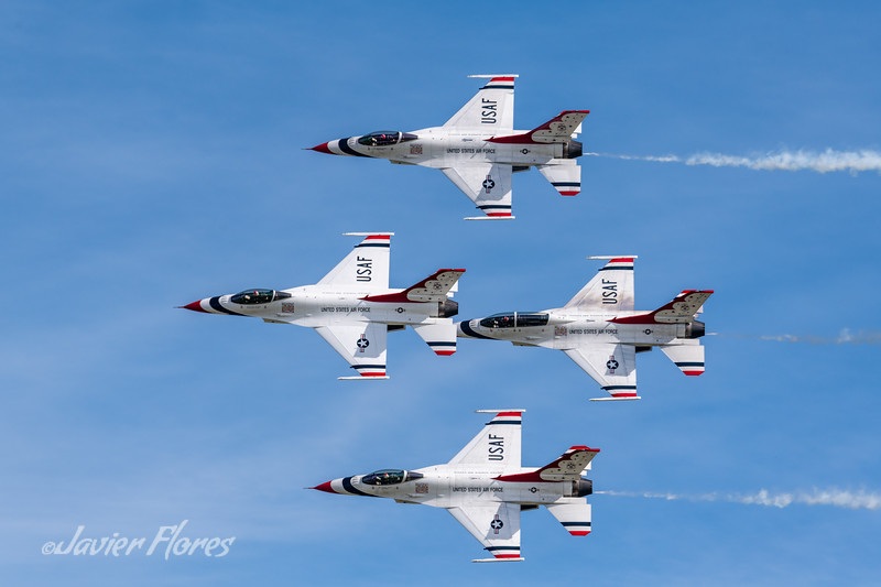 Thunderbirds flying in the diamond formation with smoke on.
