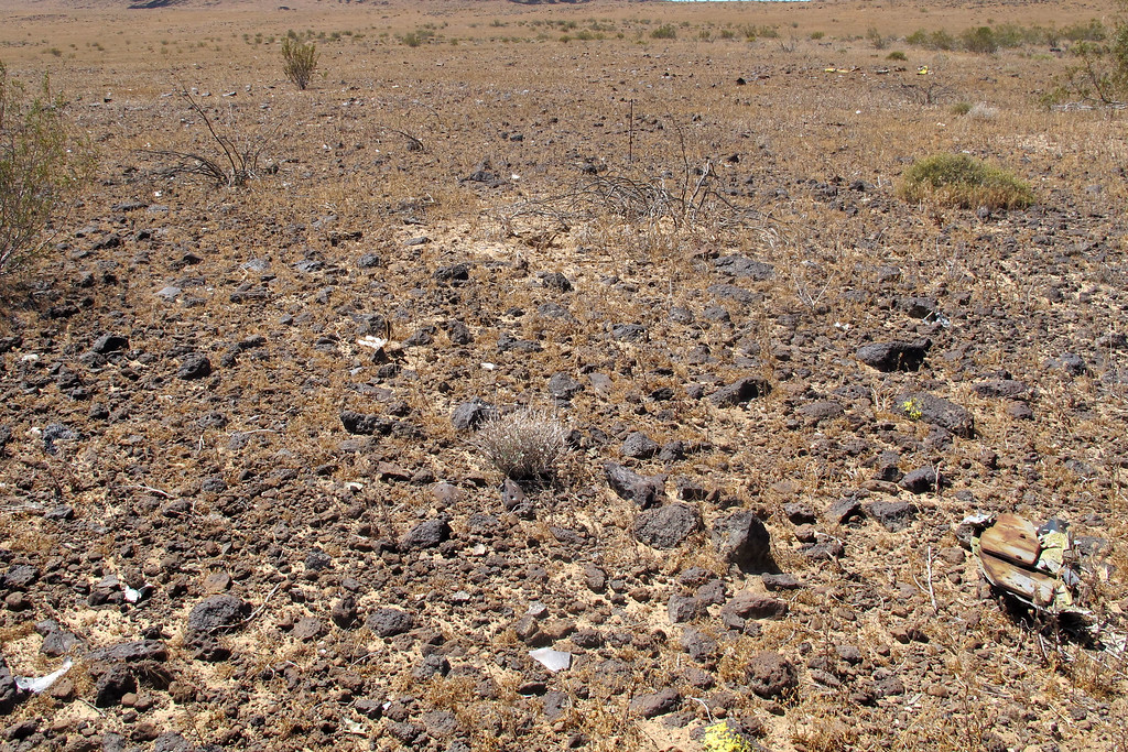 View of the debris field beyond the crater. There are hundreds of small pieces scattered for about a hundred yards in a circular pattern.