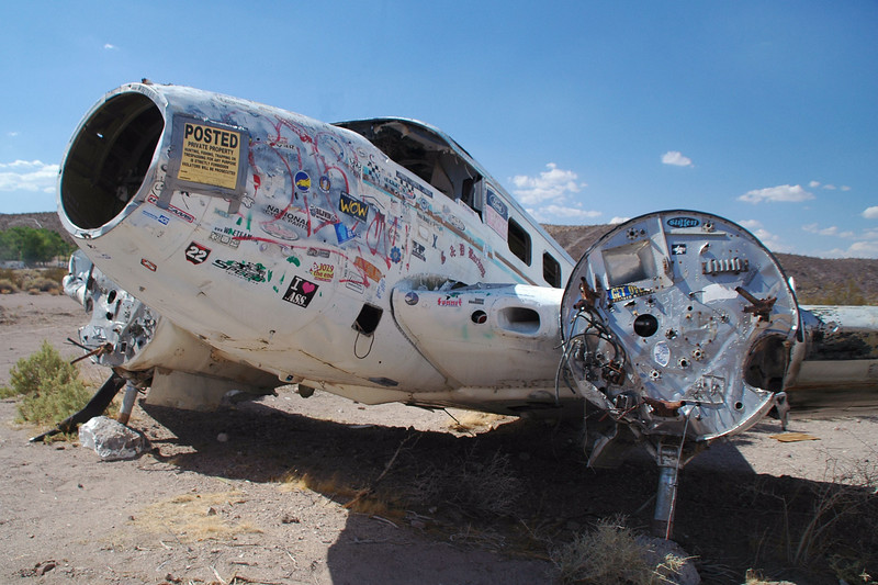 "I first saw this plane last year when driving down Hwy 95 after doing a hike in Death Valley. The sign on the nose is new. It said ""Private Property"" it had a hand written message saying not to remove parts from the plane."