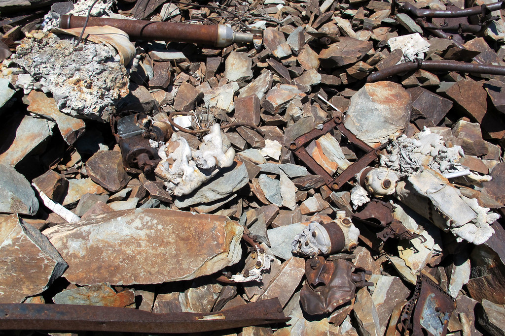 Some of the pieces and melted aluminum mixed in with the rocks.