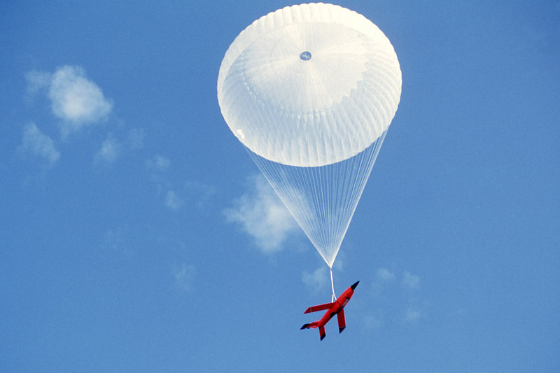 A Firebee drone returns to the ground by parachute after having served as a target for aircraft participating in the air-to-air combat training exercise.