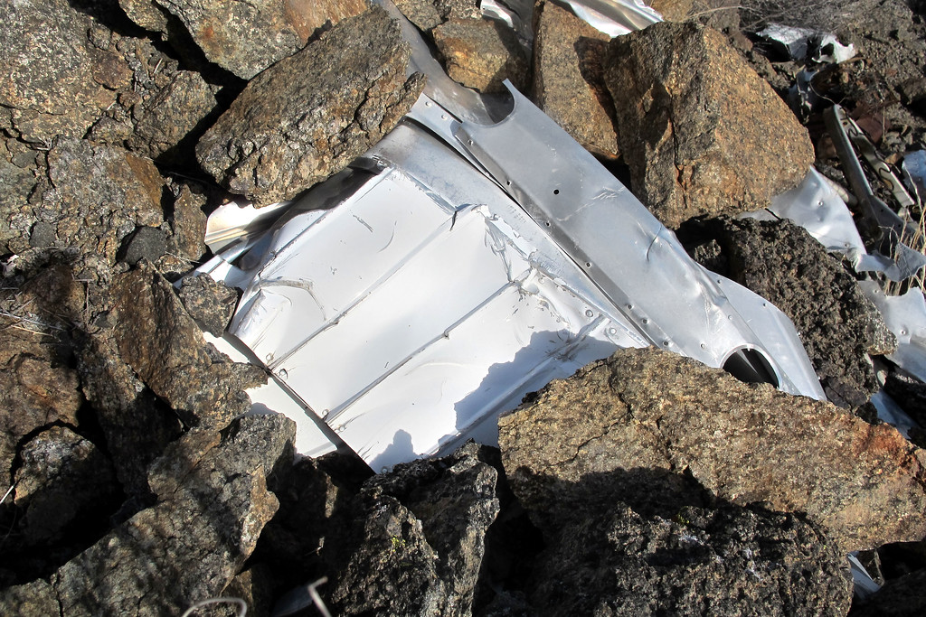 Showing from under the rocks was a section of an aileron.