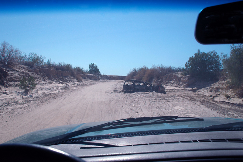 After trying to reach the site from the west for almost two hours, I gave up and tried to get to it from the east. Here I'm driving down a wash, ahead is a burned out vehicle. When I tried getting to the site from the west, I got stopped by a wash that was 30 feet arcoss and 10 feet deep. Spent an hour trying to find a way across, then on the way back to the highway, got stopped by the Border Patrol on ATVs. After searching my truck they let me go.