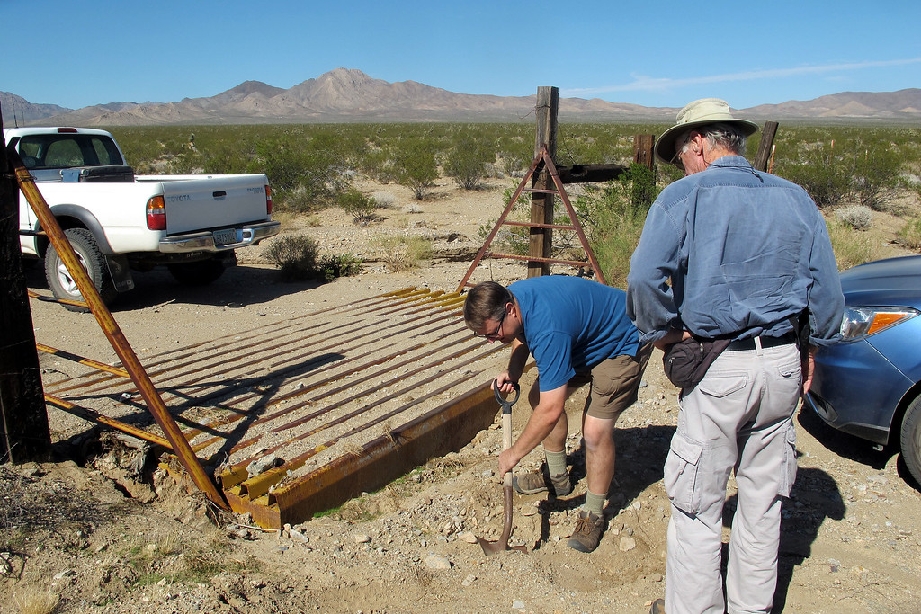 We came upon a eroded cattle grate that caused a problem for the low clearance vehicle. Craig is making a ramp for it to pass.