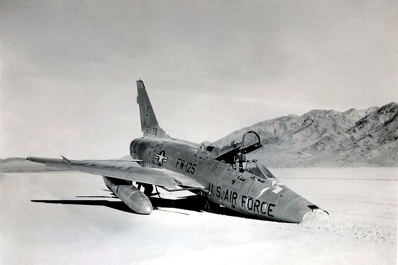 This is the F-100D #56-3125 piloted by 1Lt Douglas B. Peterson after the night time landing on Bicycle Lake at Camp Irwin. 1Lt Peterson made a good approach, but during the flare was blinded by the reflection of the his landing lights on the light surface of the runway and entered a porpoising action upon touchdown. This porpoise became violent enough to cause the collapsing of the nose gear and substantial damage to the aircraft. At the time Capt. Gerald R Weiland in #56-3058 was flying along with #56-3125 and was planning to land on the lake bed next, but #56-3125 broke the wiring to one side of the runway lights in his landing. Capt. Weiland elected to discontinue his approach and head towards Daggett Airport, but his engine shortly flamed out from lack of fuel and he was forced to eject. <br /> <br /> Photo provided by Chris Baird<br /> <br /> THE END