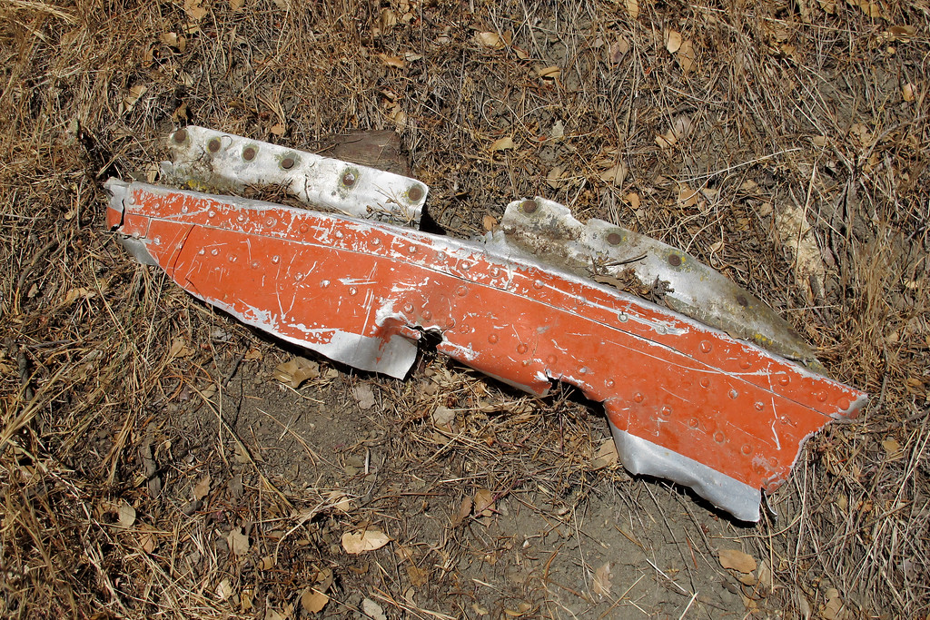 This orange piece is about thirty inches long and has wood attached to it.