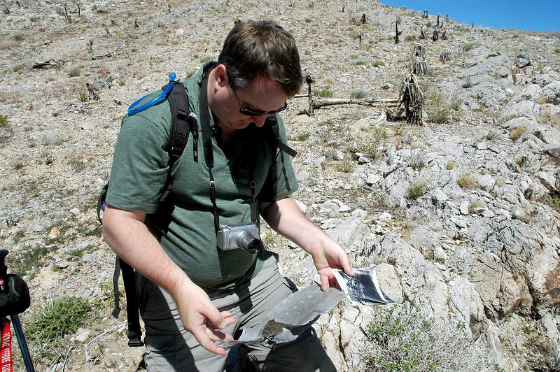 Craig checking out the piece of wreckage. In his hand are the photos he is using the locate the crash site.