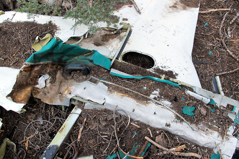 A section of the fuselage side folded flat against the wing. The rear side window can be seen above the armrest.