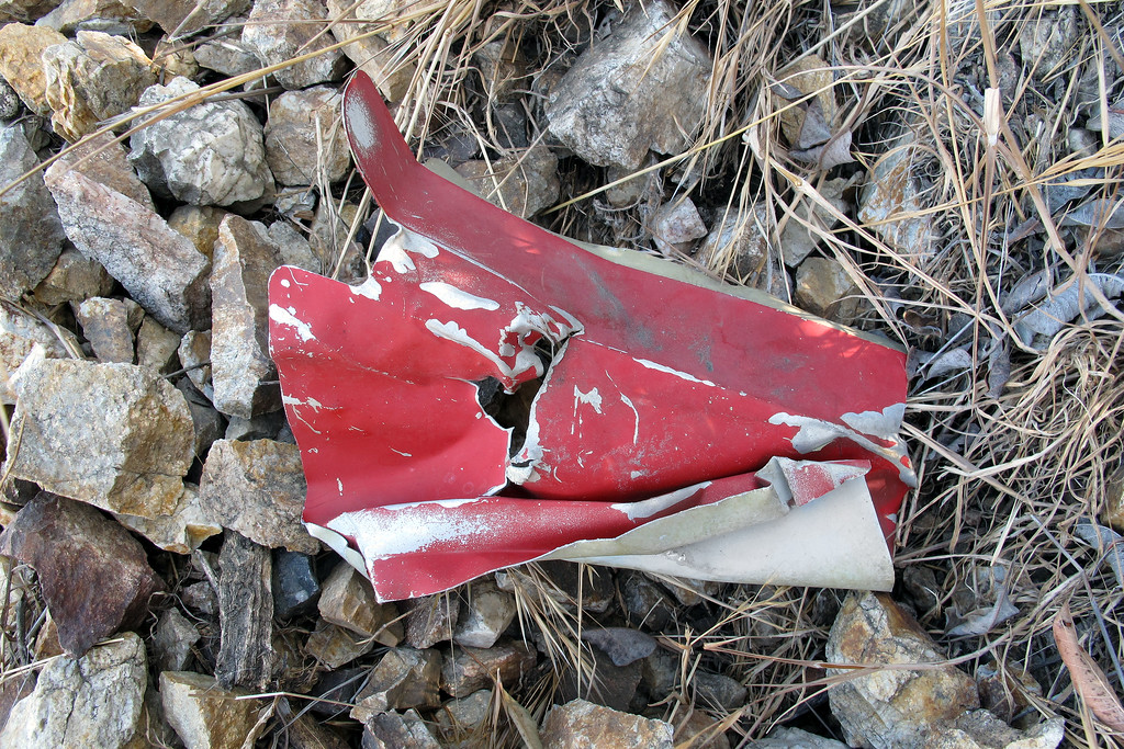 "Piece of aluminum with red paint. The CAP list has this plane as ""White/Red letters; burnt""."