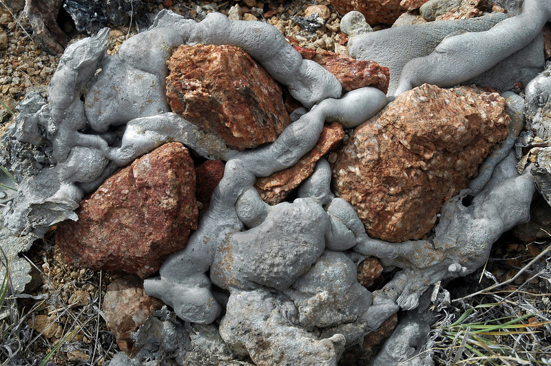 These rocks are embedded in the aluminum. There was a lot of melted aluminum at the site.
