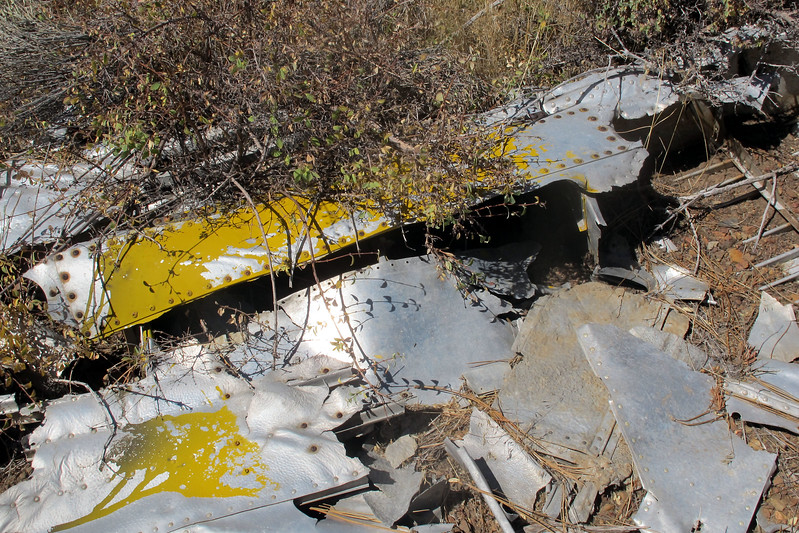 I first thought that the yellow paint was from the plane's original paint, but it looks like this was put on to marked it as a known crash site. The original paint must have burned off from past fires in the area.