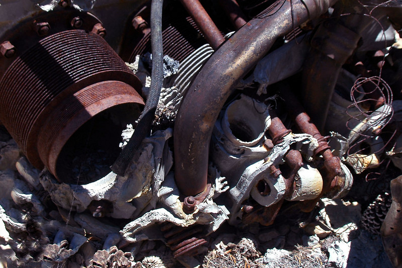 The first head is almost melted away. Only a piece with the exhaust valve remains. Rocker arms and pushrods can be seen on the second head.