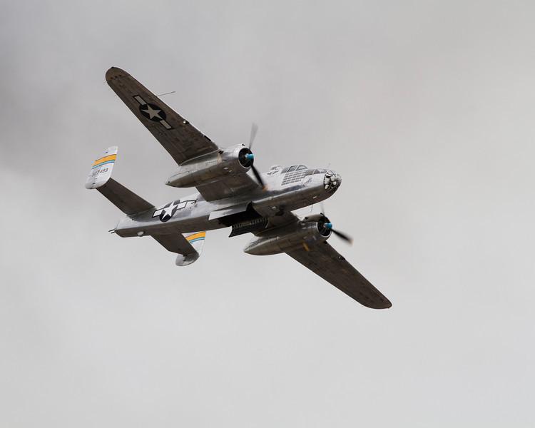 Bomb bay doors open, the B-25 flies past the crowd.