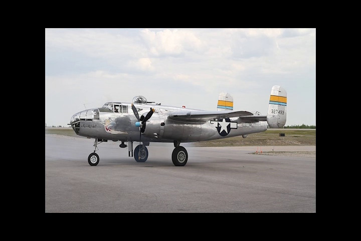 """Miss Mitchell"", a B-25 starts her engines. Once the first engines catches, a P-51 also starts its engine (to the right of the cameras position).  The B-25 will head for the taxiway and then you will see a Harvard MK IV and the P-51 Mustang. This video is 4 minutes and 29 seconds long.<br /> <br /> When finished watching the video, click on 'close' (in green above the video) to come back to the gallery."