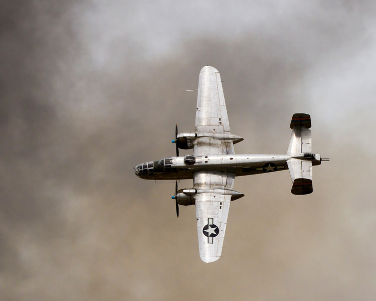 Miss Mitchell, a B-25 flies through the smoke after a simulated bomb run.