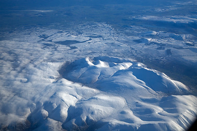 Looking east to Penrith just beyond the end of the snow cover, white smoke from a works chimney is visible.  In the centre the circular looking hills are collectively the Caldbeck Fells with summits of Carrock Fell and High Peak  with the ridge to the lower right being Saddleback or Blencathra. Coming to the bottom of the shot we see the Uldale Fells and Skiddaw Forest in the bottom right with Skiddaw itself just to the right of the window edge.