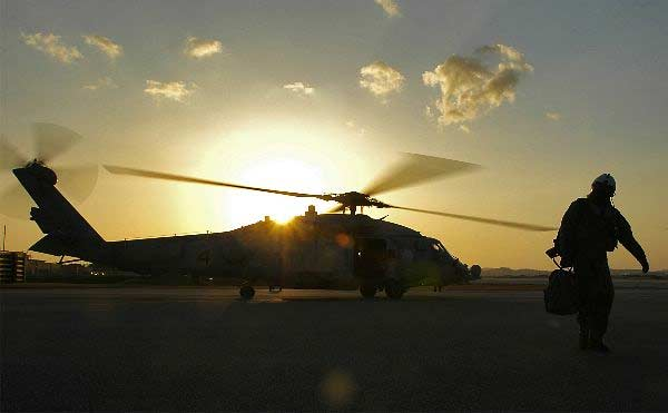 """Following an afternoon flight in support of Operation Foal Eagle, an air crewman assigned to Helicopter Anti-Submarine Squadron Two (HS-2) """"Golden Falcons"""" makes his way back to the hangar for a post flight debrief."""