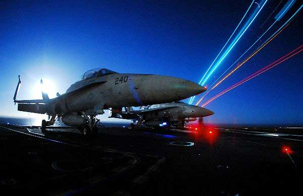 A U.S. Marine Corps F/A-18C Hornet aircraft sits chained to the flight deck aboard the Nimitz-class aircraft carrier USS John C. Stennis (CVN 74) as night flight operations take place.