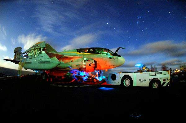 """Pilots sit in an EA-6B Prowler assigned the """"Vikings"""" of Tactical Electronic Warfare Squadron One Two Nine (VAQ-129), while flight deck crew members prepare their aircraft for night flight operations aboard the Nimitz-class aircraft carrier USS John C. Stennis (CVN 74)."""