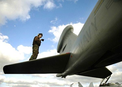 An Airman inspects the horizontal stabilizers of an EA-6B Prowler.