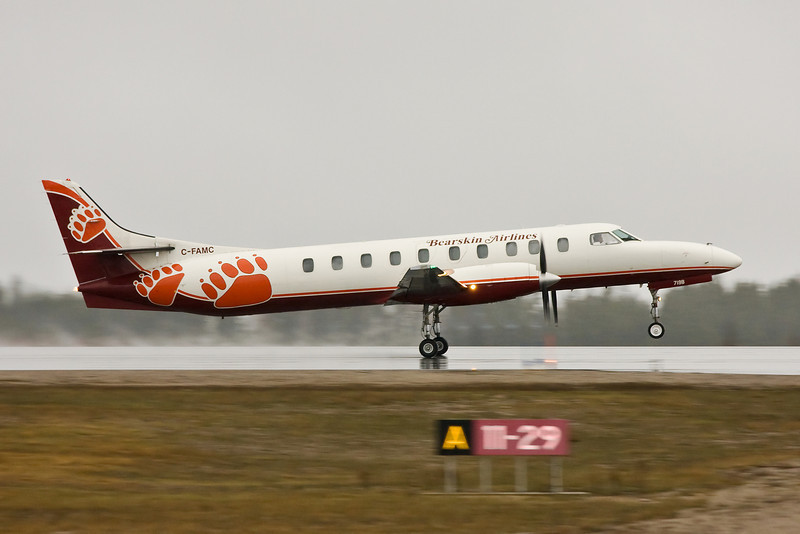 Bearskin flight JV 318 leaving Dryden in the rain.<br /> <br /> Camera incorrectly set on 'P' mode, instead of my normal shutter priority mode. The camera choose 1/200th of a second instead of 1/400th or 1/500th of a second that I would normally use.<br /> <br /> Luckily today I used for the first time my Manfrotto 679 monopod, with a Manfrotto 486RC2 ball head. I do use a image stabilized lens but panning to capture a moving train or plane and get a tack sharp photo can still be a challenge. The monopod definitely helped.