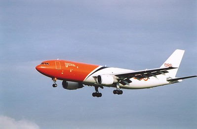 A TNT liveried Boeing 767 OO-TZC approaches the airport. The morning sun lights up the airframe against the blueish sky.