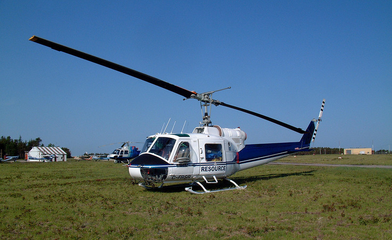 Resource sitting on the grass at Dryden with a Bell 204B.