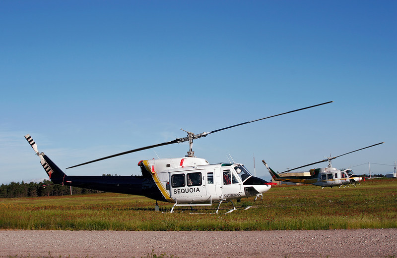 A pair of Bell 212's sit in a field next to the grass strip (runway 05-23) at the Dryden airport. C-GERH is Sequoia Helicopters Ltd and C-GSQM is Canadian Helicopters Limited.