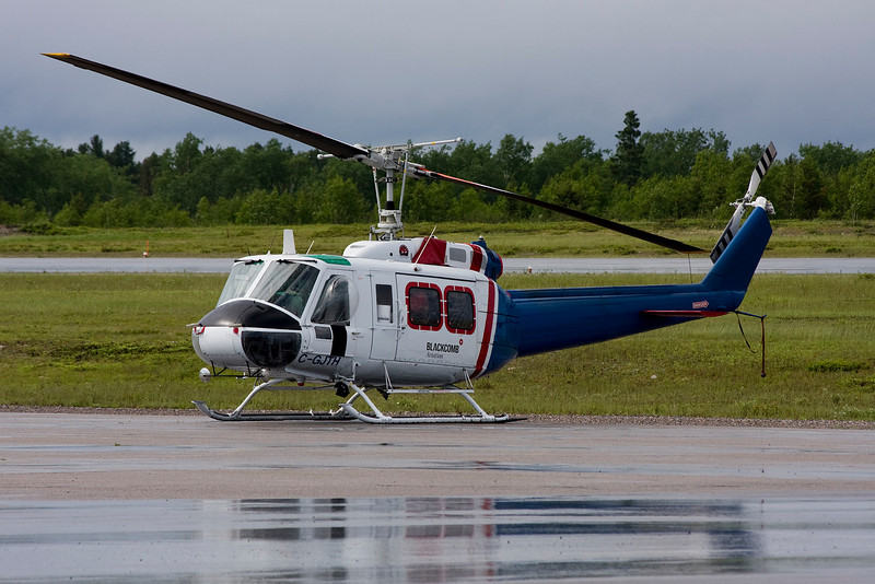 Blackcomb Aviation of Whislter BC sits on the ramp in Dryden with a Bell 205A-1 on a rainy day.