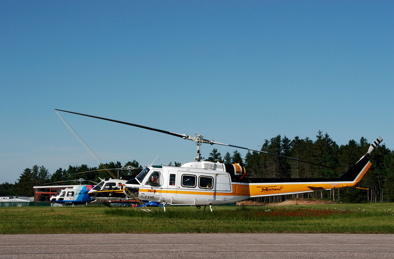 Yellowhead Helicopters Ltd (Valemount, British Columbia) waiting for a call from the MNR with a Bell 205A-1 at the Dryden airport. <br /> <br /> In the background you can see  C-GWDT, a Aerospatiale AS 350 B-2 owned by Day & Johnston Helicopters Ltd. You can also see C-FYZF, an Aerospatiale AS350 B3 from Great Slave Helicopters Ltd.<br /> <br /> Interesting to note, the registration of C-FYHD - YHD is the airport code for Dryden.<br /> <br /> Well, *I* thought it was interesting.