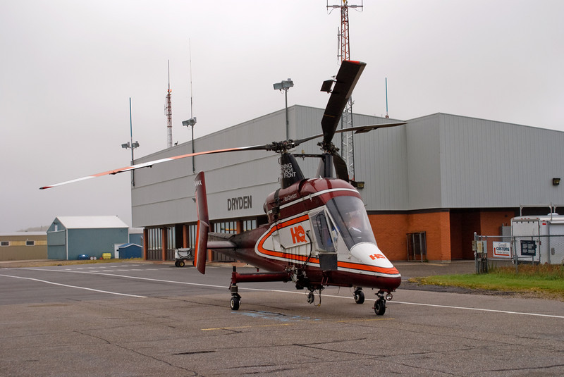 A Kaman K-1200 owned by Heliqwest Aviation Inc. is in the Dryden area doing some work for Hydro. Here they are sitting on the Dryden ramp waiting for fuel with a overcast sky.