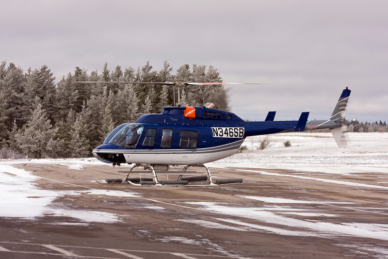 A Bell 206L with an American ident about to lift off from Dryden.