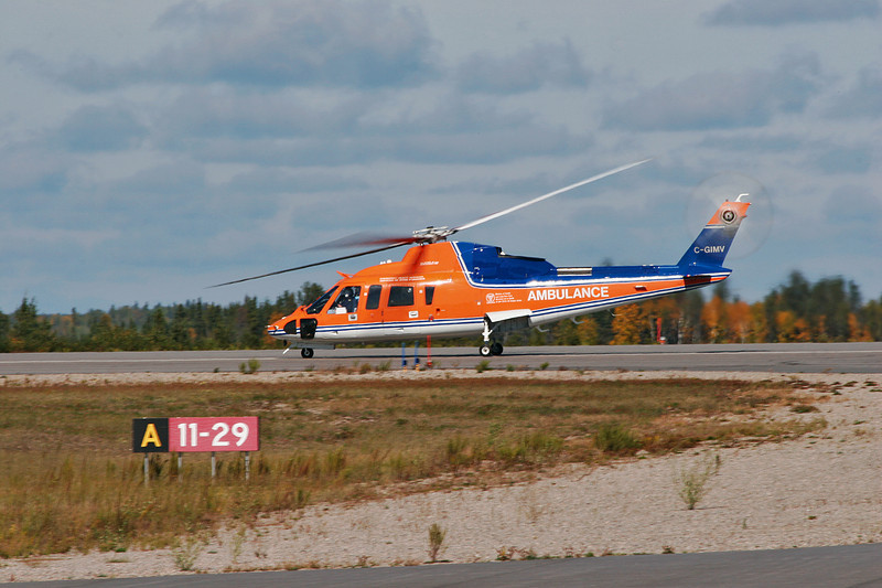 A Sikorsky S-76A owned by Canadian Helicopters (C-GIMV) about to lift off from runway 29.