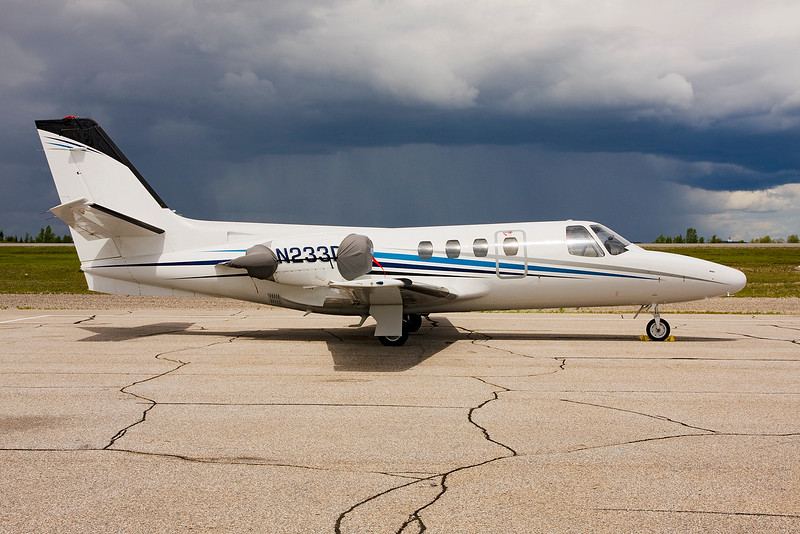 A Cessna 500-0158 (N233DB) from Nashville TN sits on the Dryden ramp as a heavy rain shower skirts by the airport.