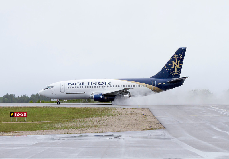 Nolinor stopping on a wet runway during a drab, wet, overcast day.