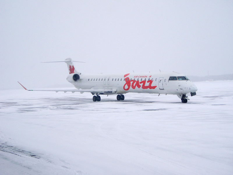 Due to a situation at another airport, this Jazz flight had to divert to Dryden in what turned out to be a really lousy day weather wise. The snow was not sticking to the aircraft so I didn't have to de-ice. <br /> <br /> I didn't have any of my cameras handy so I had to use Wendys point and shoot digi. It can be hard to take a photo of a white plane while it snows.<br /> <br /> After sitting on the ramp for a couple hours, they left for their final destination.