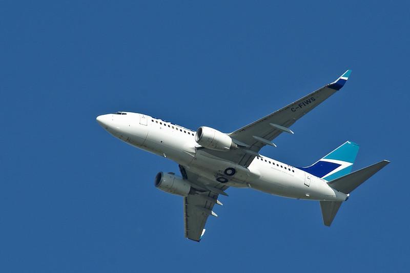 A Westjet Boeing 737-76N. Photo taken from the Winnipeg Zoo.