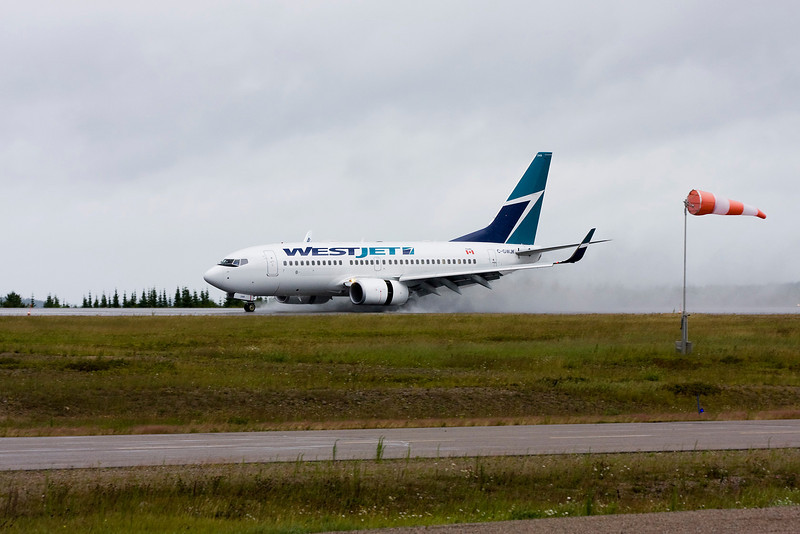 Normally I would not want the wind sock in the photo but with the overcast sky, the wet runway - you can see that it was a lousy day today as Westjet landed in Dryden for a MNR charter.