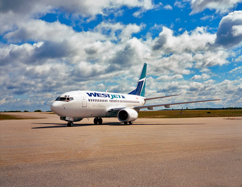 A WestJet Boeing 737-700 taxis into position on the Dryden ramp during a MNR fire fighter charter.<br /> <br /> An unmetered photo taken with a Fuji GW670II.