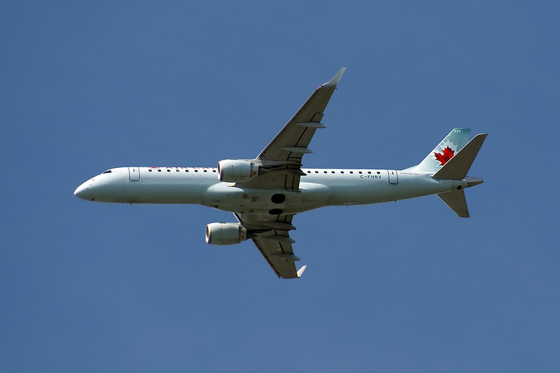 A Air Canada Embraer ERJ 190-100 IGW  leaves the Winnipeg airport. Photo taken from within the Winnipeg Zoo.