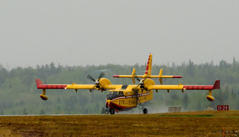 A Canadair CL-415 (CL215 6B11), tanker 270, leaves Dryden on runway 29. Only to return a half hour later.<br /> <br /> The photo is not razor sharp as the aircraft was a half of a mile away, and it was raining. Light levels where also low due to being overcast. The purpose of the photo was to try and capture the vortices. <br /> <br /> This photo was taken with a slower than normal shutter speed of 1/320th of a second at F13 (on purpose) to better capture the vortices, and to give a slight blur to the propellers. This is also a small crop of the original photo.
