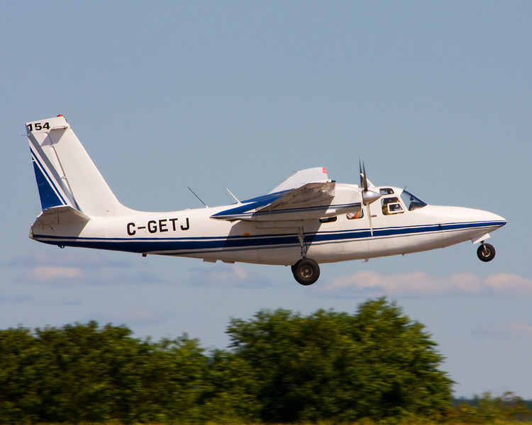A Aero Commander 500S (owned by  Hicks & Lawrence Limited of Dryden, ON) takes off from runway 11 of the Dryden airport.