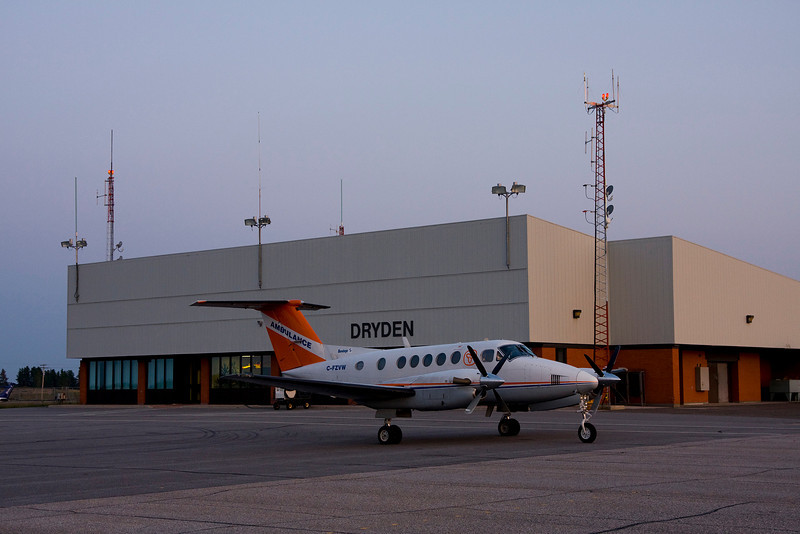 An air ambulance (Bandage 5) sits on the Dryden ramp waiting for the land ambulance to arrive. Photo was taken in the evening with the sun quite low in the sky (20:41).<br /> <br /> In the terminal window (just behind the aircraft) you can see a model of a CL-215.