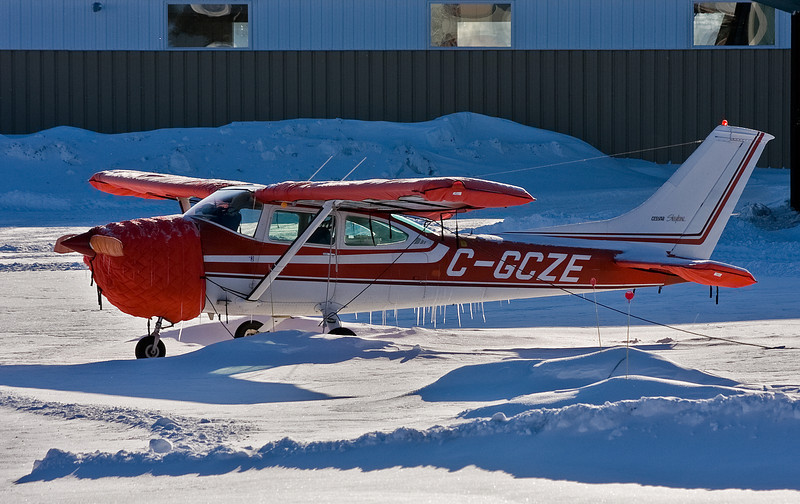 A Cessna	182P sitting in the snow. I see there are a lot of icicles. Does that mean spring might be around the corner?